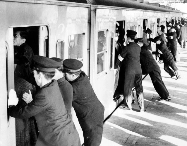 """College students employed as uniformed """"pushers"""" cram commuters into railroad passenger cars in Tokyo. (Photo by Library of Congress via The Atlantic)"""