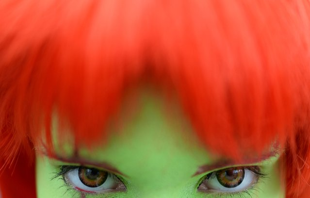 A female cosplayer with red hair and colored contact lenses looks at the photographer at the Leipzig Book Fair, in Leipzig,Germamy, March 15, 2014.  Around 2,000 publishing houses will present their newest publications at the book fair until March 16. Cosplaying is a Japanese costuming trend. (Photo by Hendrik Schmidt/EPA)