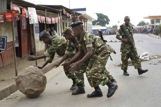 Soldiers clear a roadblock set by demonstrators in the Cibitoke neighborhood of Bujumbura, Burundi, Friday May 22, 2015. Two protesters in Burundi were shot dead Thursday, said the Red Cross, as pitched battles in the capital escalated between police and demonstrators opposed to President Pierre Nkurunziza's bid for a third term. (Photo by Jerome Delay/AP Photo)
