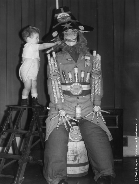 1940: A young toddler adds the finishing touches to an effigy of Guy Fawkes on Guy Fawkes Night