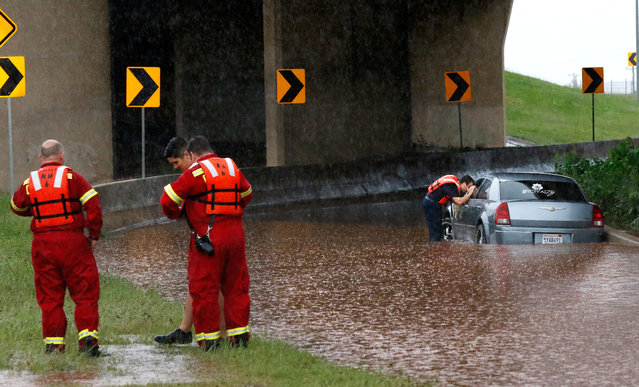 A firefighter looks into the window of a partially submerged car, checking to see if anyone is inside, Saturday, May 23, 2015, in Oklahoma City. The Oklahoma Department of Transportation said at least 15 highways have been closed across the state due to high water from the recent flooding. (Photo by Jim Beckel/The Oklahoman via AP Photo)
