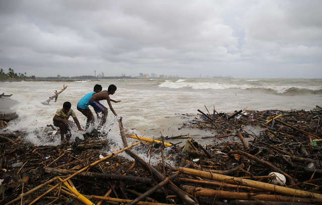 Sri Lankans look for recyclable material washed ashore with stormy waves in Colombo, Sri Lanka, Monday, May 21, 2018. Heavy rain and lightning strikes across Sri Lanka have left at least five people dead and displaced more than 1,000, officials said Monday. (Photo by Eranga Jayawardena/AP Photo)