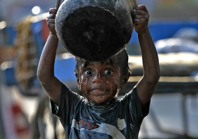 A boy takes a bath along a pavement in the southern Indian city of Chennai March 22, 2014. World Water Day is celebrated on March 22. (Photo by Reuters/Babu Babu)