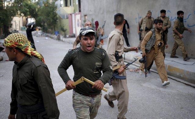 Kurdish gunmen run on a street during clashes with Shi'ite militia in Tuz Khurmato, Iraq, April 24, 2016. (Photo by Goran Tomasevic/Reuters)