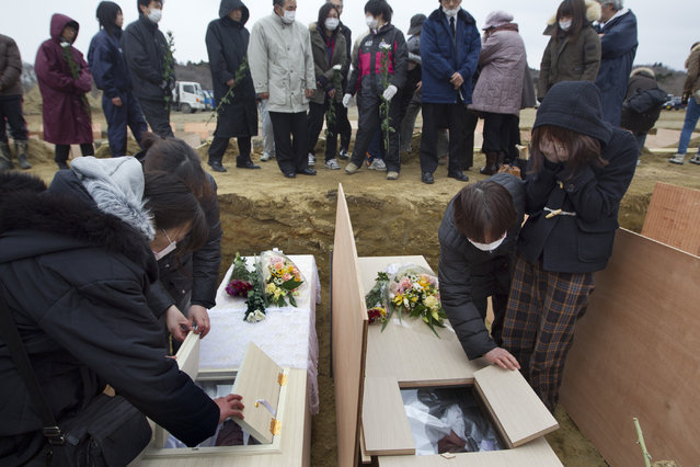 Families and relatives of the dead cry as they identify their family members at a temporary burial ground March 25, 2011 in Higashi Matsushima , Japan.  Under Japanese Buddhist practice a cremation is the expected traditional way of dealing with the dead but now with the death toll so high crematoriums are overwhelmed and there is a shortage of fuel to burn them. Local municipalities are forced to dig mass graves as a temporary solution. Two weeks after the magnitude 9 earthquake and tsunami struck Japan the death toll has risen to 10,000 dead with still thousands missing and the expectation is that it will end up well over 20,000. Presently the country is still struggling to repair a damaged nuclear power plant that has caused tremendous problems, evacuations, and now tainted water supply in the Tokyo area causing more panic buying of bottled water. (Photo by Paula Bronstein/Getty Images)