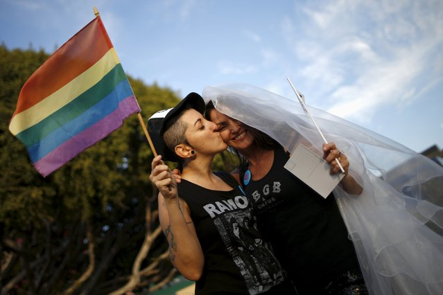 Natalie Novoa, 38, (L) kisses her wife Eddie Daniels at a celebration rally after getting married in West Hollywood, California, United States, June 26, 2015. (Photo by Lucy Nicholson/Reuters)