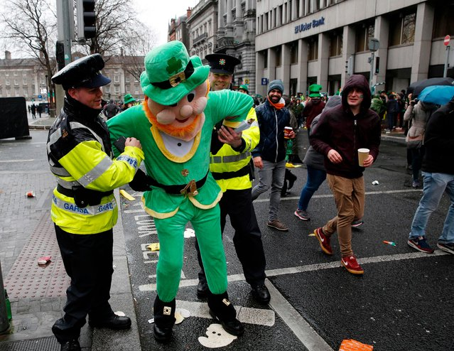 Police officers pretend to arrest a man dressed in a leprechaun outfit as he poses for a photograph along the parade route during the St. Patrick' s Day parade in Dublin, Ireland on March 17, 2017. (Photo by Adrian Dennis/AFP Photo)