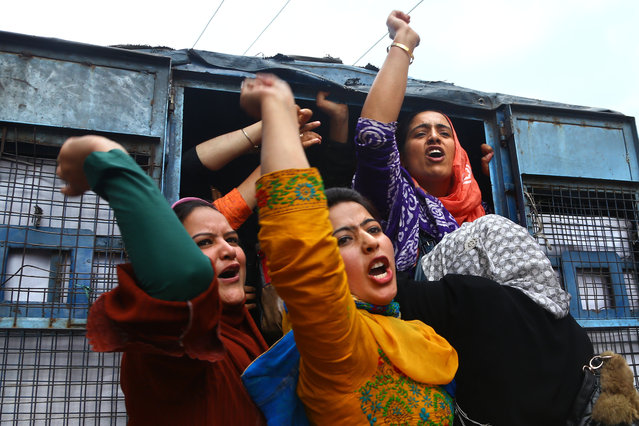 Kashmiri women employees of National Health Mission (NHM) shouts slogans from a police vehicle after being detained during a protest in Srinagar, Indian controlled Kashmir, Saturday, May 23, 2015. Police detained dozen of NHM employees who were demanding regularization of their jobs. (Photo by Dar Yasin/AP Photo)
