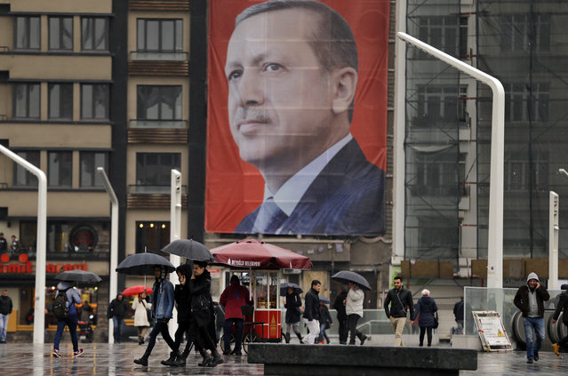 In this Tuesday, March 14, 2017 photo, people walk in central Istanbul's Taksim Square, backdropped by a poster of Turkish President Recep Tayyip Erdogan. The entire Turkish referendum campaign has been biased and unfair, those opposed to expanding the president's powers say, noting they have been hampered by a lack of TV airtime, threats, violence, arbitrary detentions and even sabotage. Those reports come even as Erdogan himself has slammed European countries for not letting his ministers campaign on their soil for the April 16 vote on expanding his powers. (Photo by Lefteris Pitarakis/AP Photo)
