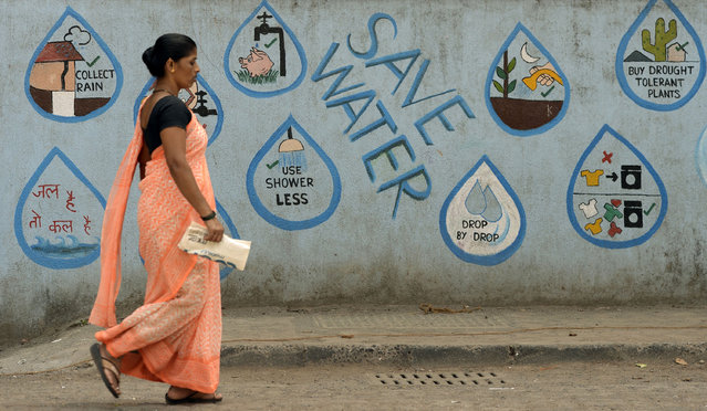 An Indian pedestrian walks past a wall adorned with water conservation messages in Mumbai on March 22, 2017, on World Water Day. Recycling the world's wastewater, almost all of which goes untreated, would ease global water shortages while protecting the environment, the United Nations said in a major report. (Photo by Punit Paranjpe/AFP Photo)