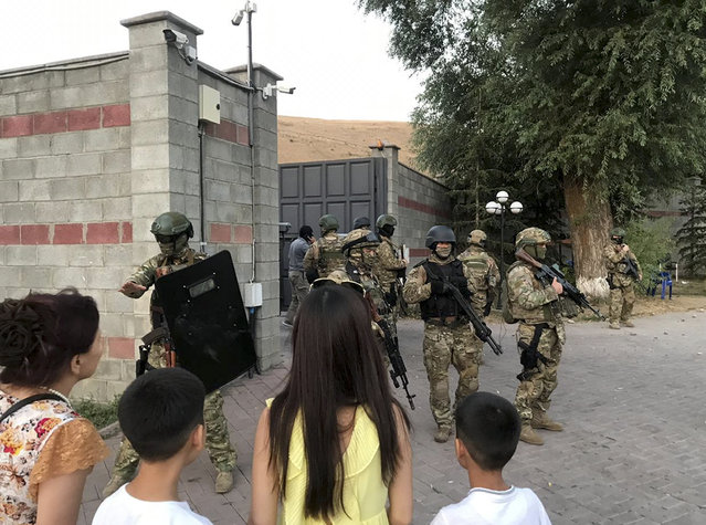 Kyrgyz special forces stand in guard at former president of Kyrgyzstan Almazbek Atambayev's residence in the village of Koi-Tash, about 20 kilometers (12 miles) south of the capital, Bishkek, Kyrgyzstan, Wednesday, August 7, 2019. Gunfire is being heard outside the residence of the former president of Kyrgyzstan as police move in to try to arrest him. The Kyrgyz news site 24.kg said several people, including journalists, have been wounded in the Wednesday shooting in the village of Koi-Tash, 20 kilometers (12 miles) south of the capital, Bishkek. (Photo by AKIpress via AP Photo)