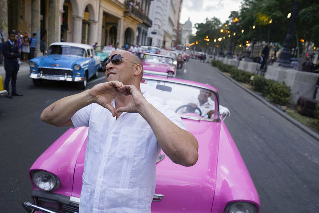 "U.S. Actor Vin Diesel gestures to the crowd watching the presentation of fashion designer Karl Lagerfeld's ""cruise"" line for fashion house Chanel, at the Paseo del Prado street in Havana, Cuba, Tuesday, May 3, 2016. With the heart of the Cuban capital effectively privatized by an international corporation under the watchful eye of the Cuban state, the premiere of Chanel 2016/2017 ""cruise"" line offered a startling sight in a country officially dedicated to social equality and the rejection of material wealth. (Photo by Ramon Espinosa/AP Photo)"