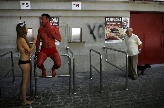 Animal rights protesters talk before a demonstration calling for the abolition of bull runs and bullfights, three days before the start of the famous running of the bulls San Fermin festival in Pamplona, northern Spain, July 4, 2015. (Photo by Eloy Alonso/Reuters)