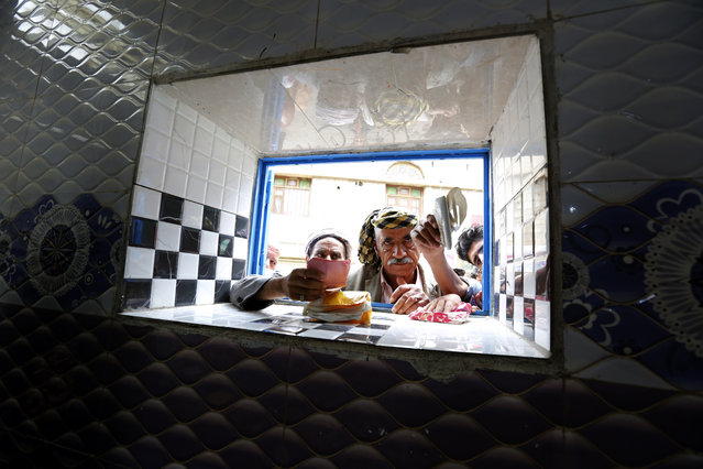 Conflict-affected men wait to get free bread provided by a local charity bakery during the holy fasting month of Ramadan in Sana'a, Yemen, 18 May 2019. Muslims around the world celebrate the holy month of Ramadan by praying during the night time and abstaining from eating, drinking, and sexual acts during the period between sunrise and sunset. Ramadan is the ninth month in the Islamic calendar and it is believed that the revelation of the first verse in Koran was during its last 10 nights. (Photo by Yahya Arhab/EPA/EFE)