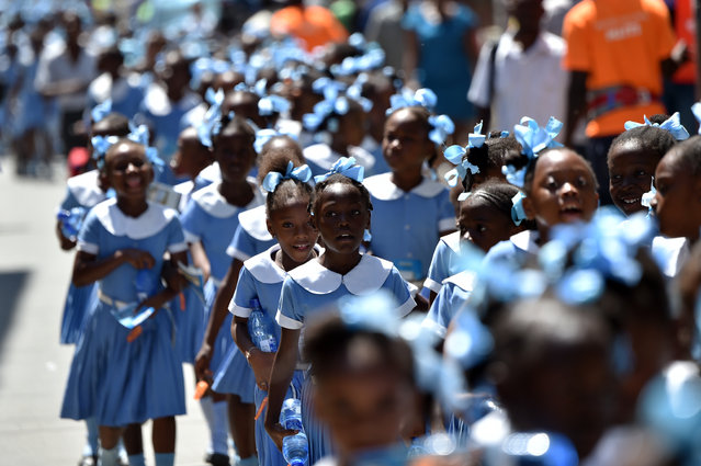 Haitian students walk as they head to a security zone during an Earthquake and Tsunami Emergency drill in the city of Cap-Haitien, on May 6, 2016. The simulation exercise was organised by the Civil Protection Directorate, with the support of the UN Development Programme (UNDP). An estimated 4,500 people participated in the activities during the simulacre. (Photo by Hector Retamal/AFP Photo)