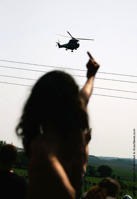 An activist of the anti-G8 forum 'Block G8' shows his middle finger to a police helicopter passing overhead