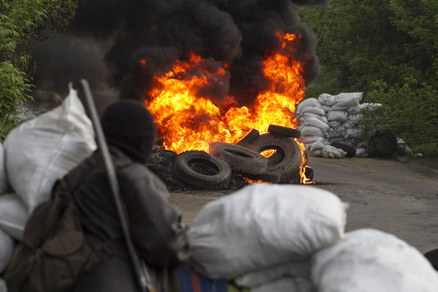 A pro-Russian separatist guards a checkpoint as tyres burn in front of him, near the town of Slaviansk in eastern Ukraine May 2, 2014. (Photo by Baz Ratner/Reuters)