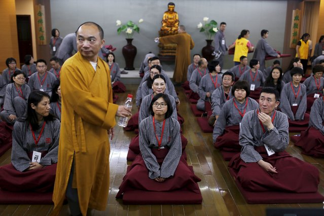 "A Buddhist monk stands in front of participants attending a class at Yufo Buddhism Temple in Shanghai, China, July 8, 2015. About 70 Shanghai residents took part in the two-day ""zen"" class at the temple on Wednesday, which required them to lock away their mobile phones, tablet devices and other belongings so that they could concentrate on the study of Buddhism. (Photo by Aly Song/Reuters)"