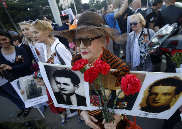 A woman holds a pictures of her relatives killed in WWII, during the Victory Day ceremony, in Belgrade, Serbia, Monday, May 9, 2016. People flocked to memorial cemetery to the liberators of Belgrade marking the 71th anniversary of the victory over Nazi Germany in WWII. (Photo by Darko Vojinovic/AP Photo)