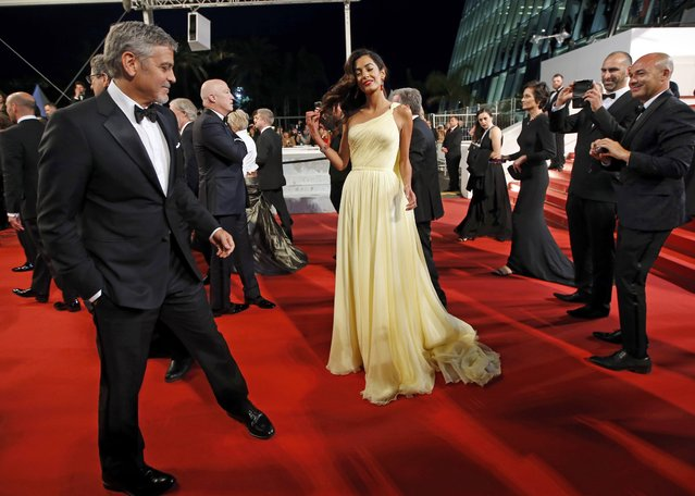 """Cast member George Clooney and his wife Amal pose on the red carpet after the screening of the film """"Money Monster"""" out of competition at the 69th Cannes Film Festival in Cannes, France, May 12, 2016. (Photo by Jean-Paul Pelissier/Reuters)"""