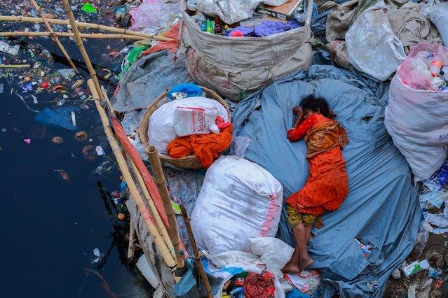 Sleep Fatigue by Amdad Hossain, Dhaka, Bangladesh. A women sleeps on a dirty riverbank. (Photo by Amdad Hossain/CIWEM Environmental Photographer of the Year 2019)