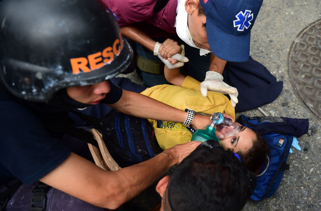 Rescue workers assist a woman after clashes with the riot police during a protest against Venezuelan President Nicolas Maduro, in Caracas on April 20, 2017. (Photo by Ronaldo Schemidt/AFP Photo)