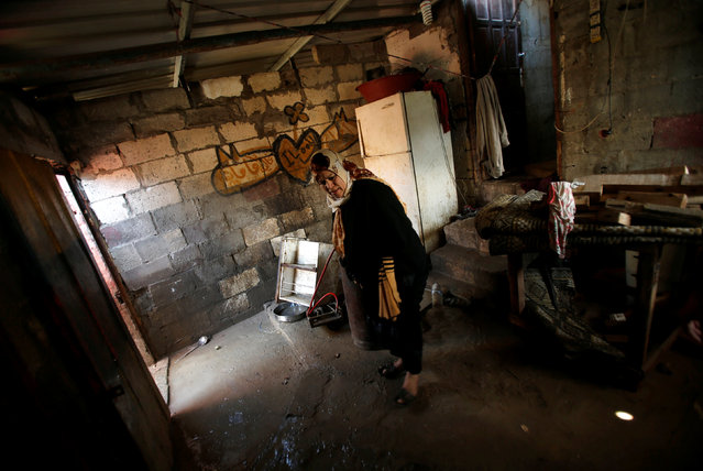 A Palestinian woman inspects her shelter that was flooded during a rainstorm, in the northern Gaza Strip February 17, 2017. (Photo by Mohammed Salem/Reuters)