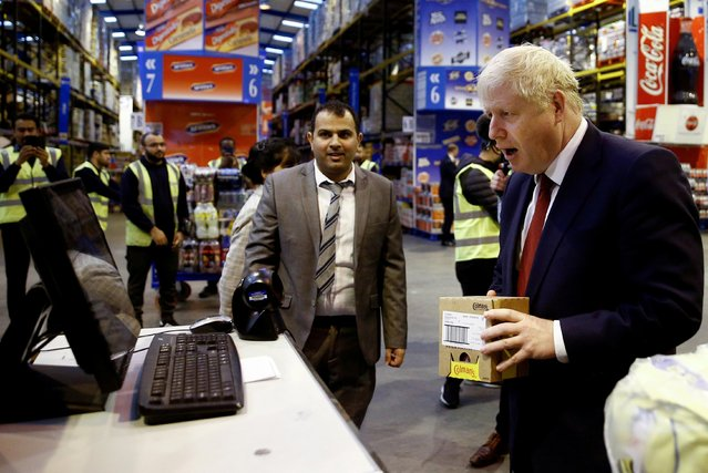 Britain's Prime Minister Boris Johnson reacts as he scans an item during a visit to Bestway Wholesale in Manchester, Britain on September 30, 2019. (Photo by Henry Nicholls/Reuters/Pool)