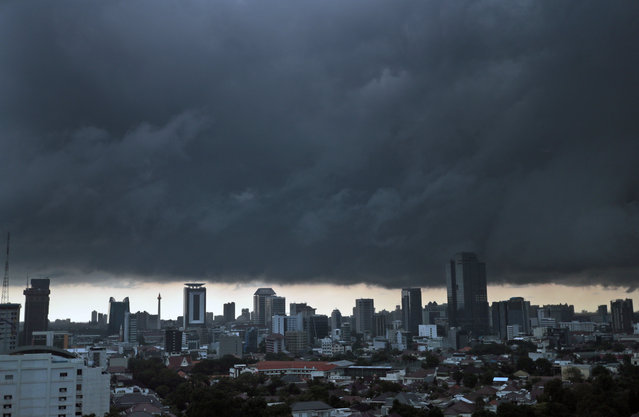 Ominous storm clouds hover over the main business district prior to a downpour in Jakarta, Indonesia, Tuesday, April 2, 2019. (Photo by Dita Alangkara/AP Photo)
