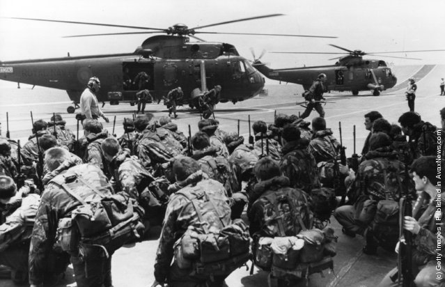 A View of commandos being lifted from the decks of HMS Hermes and HMS Invincible to be transferred by Westland Sea King helicopters to other ships while two aircraft carriers forge ahead to the Falkland Islands from Ascension Island, leaving the marines ready to move at short notice