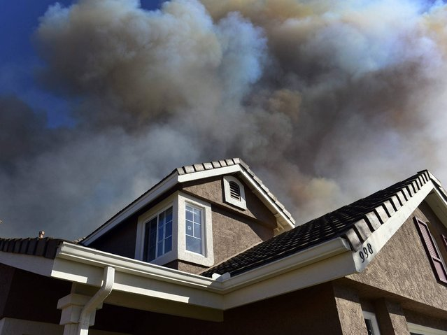Smoke from a nearby fire billowing behind homes in San Marcos, in the San Diego county, California. (Photo by Stuart Palley/EPA)