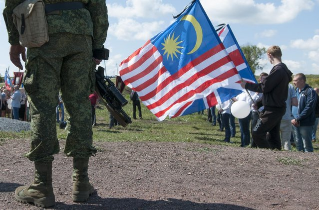 People holding flags of countries of the victims who were killed in the crash of the Malaysia Airlines Flight 17, attend a memorial ceremony at the crash site near the village of Hrabove, eastern Ukraine, Friday, July 17, 2015. (Photo by Antoine E. R. Delaunay/AP Photo)