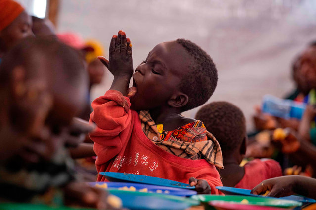 Young Burundian refugee, Kevin licks his hand as he enjoys a meal on October 3, 2019 at the Nyabitara Transit site in Ruyigi, Burundi. Nearly 600 Burundians who fled political violence in their home country to Tanzania were on Thursday repatriated voluntarily, the UN refugee agency and witnesses said. The move came after the Tanzanian government vowed that from October 1 it would start repatriating all Burundians, willing or not – a stance that some officials appeared to be trying to roll back. (Photo by Tchandrou Nitanga/AFP Photo)