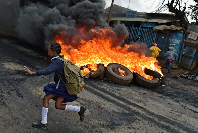 A schoolgirl runs past a burning barricade in Kibera slum, Nairobi on May 23, 2016 during a demonstration of opposition supporters protesting for a change of leadership ahead of a vote due next years. (Photo by Carl De Souza/AFP Photo)