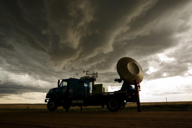 The Doppler on Wheels (DOW) vehicle scans a supercell thunderstorm during a tornado research mission, May 8, 2017 in Elbert County near Agate, Colorado. Doppler on Wheels (DOW) is a mobile doppler radar mounted on a truck that brings instruments directly into storms, allowing scientists to scan storms and tornadoes and make 3-D maps of wind and debris. (Photo by Drew Angerer/Getty Images)