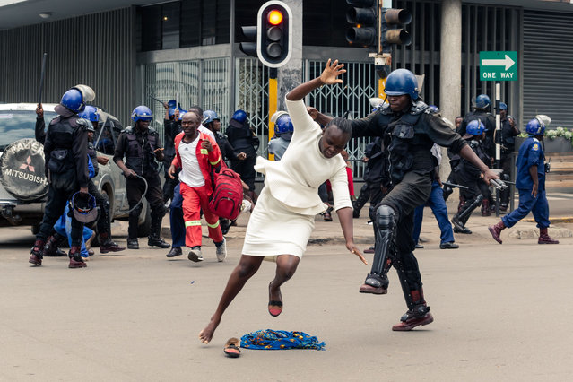 An anti-riot police man in Zimbabwe tackles a woman with his boot as they dispersed a crowd gathered to hear an address by leader of the MDC (Movement for Democratic Change) Alliance, Nelson Chamisa at Morgan Tsvangirai House, the party headquarters, in Harare, on November 20, 2019. Nelson Chamisa was due to address party supporters in his Hope of the Nation Address (HONA). The public address was blocked by riot police who beat up several people as they dispersed MDC supporters and other curious onlookers. (Photo by Jekesai Njikizana/AFP Photo)