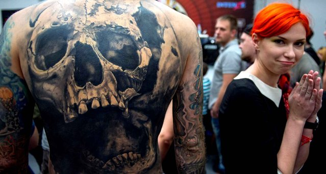 A woman reacts next to a man's tattooed back depicting a skull, during the Moscow International Tattoo Week in Moscow on July 25, 2015. (Photo by Alexander Utkin/AFP Photo)