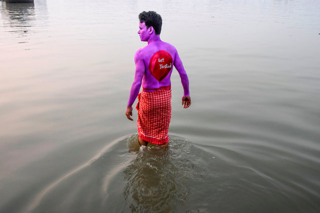 "A volunteer goes into water to wash his painted body after he participated in an awareness event on the eve of the ""World AIDS Day"" in Kolkata on November 30, 2019. (Photo by Dibyangshu Sarkar/AFP Photo)"