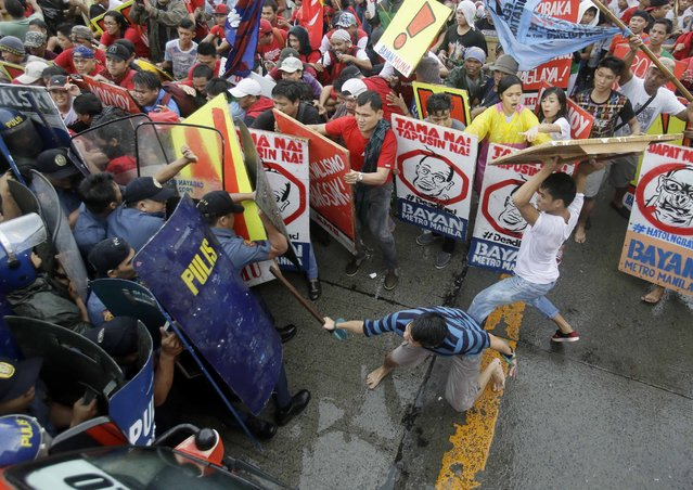"Protesters clash with police as they try to force their way closer to the House of Representatives to coincide with the last State-of-the-Nation-Address or SONA of Philippine President Benigno Aquino III at suburban Quezon city northeast of Manila, Philippines Monday, July 27, 2015. The protesters assailed  the Aquino administration for its alleged failures to address the ""lingering problems"" of the people. (Photo by Bullit Marquez/AP Photo)"