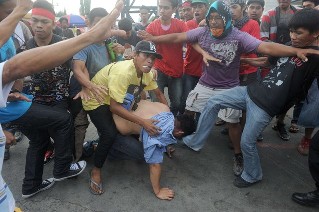 Protesters mob a suspected undercover policeman (C) at a rally in suburban Manila on July 27, 2015, hours before President Benigno Aquino delivers his final annual address to parliament. Aquino is expected to report on his six-year term as well as sketch a roadmap for his successor to be elected in the May 2016 elections. (Photo by Jay Directo/AFP Photo)