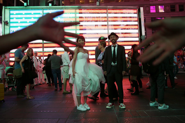 People try to block photos being taken of a newly married couple from Japan as they pose for photos for their wedding photographer in Times Square in the Manhattan borough of New York, U.S., May 25, 2016. (Photo by Carlo Allegri/Reuters)