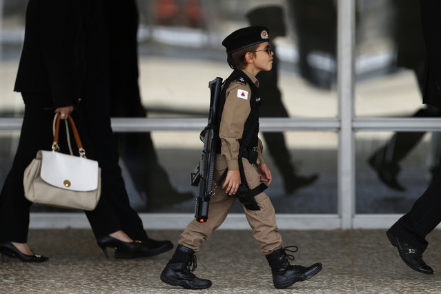 A boy dressed in a military police costume arrives to watch the Changing of the Guard at the Planalto Presidential Palace, in Brasilia, Brazil, Thursday, November 28, 2019. (Photo by Eraldo Peres/AP Photo)