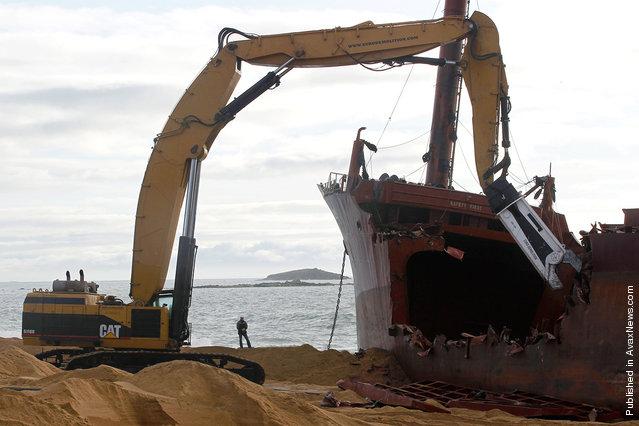 A hydraulic shear cuts apart the hull, dismantling the TK Bremen on Kerminihy beach, on January 7, 2012