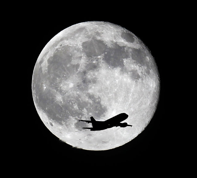 An American Airlines passenger airplane from Miami crosses a blue moon over Whittier, Calif., as it heads to Los Angeles Airport, Friday, July 31, 2015. (Photo by Nick Ut/AP Photo)
