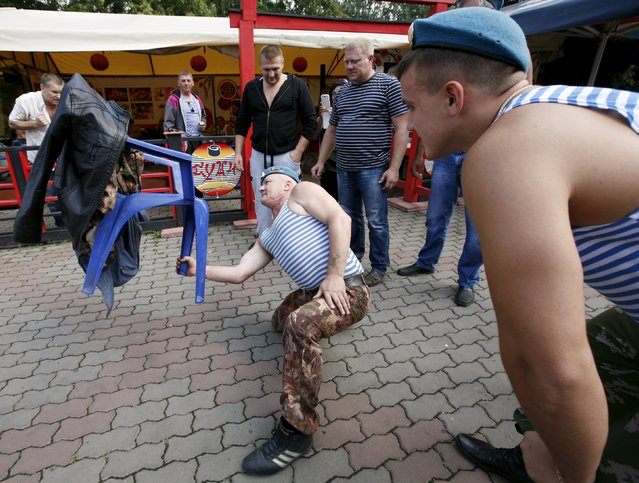 A former paratrooper demonstrates his strength and skills while lifting a chair during the celebrations for the Paratroopers Day at the Central park in the Siberian city of Krasnoyarsk, Russia, August 2, 2015. (Photo by Ilya Naymushin/Reuters)
