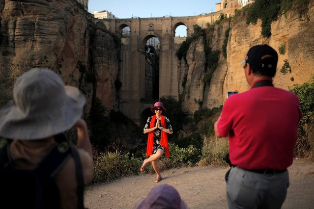 "A Chinese tourist gestures as she is photographed by compatriots in front of the ""Puente Nuevo"" (New Bridge) in Ronda, southern Spain, June 8, 2016. (Photo by Jon Nazca/Reuters)"