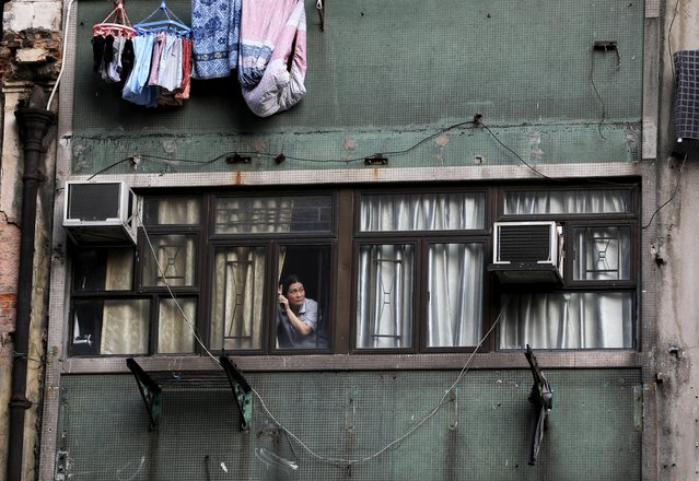 A woman looks out of a window during an anti-government protest in Hong Kong, October 20, 2019. (Photo by Ammar Awad/Reuters)