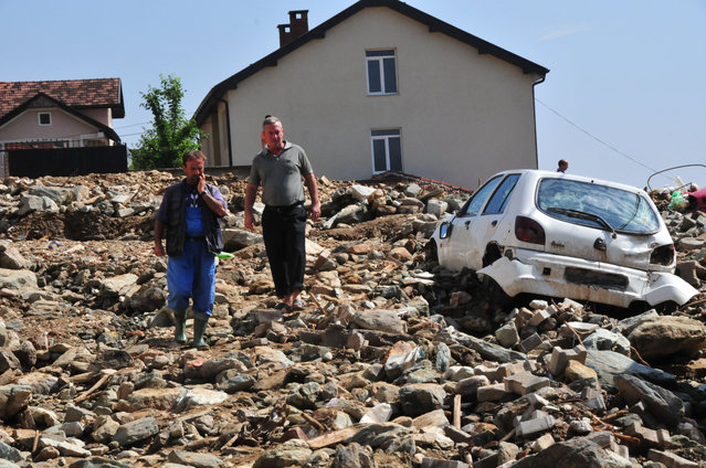 People walk  over mud, rocks and debris piled after a flood in the village of Golema Recica, just near the town of Tetovo, in northwestern Macedonia, on Tuesday, August 4, 2015. (Photo by Zoran Andonov/AP Photo)