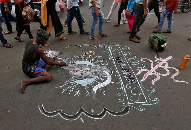 A man sketches a portrait of Hindi Lord Shiva to earn money alongside a road in Kolkata, June 22, 2017. (Photo by Rupak De Chowdhuri/Reuters)