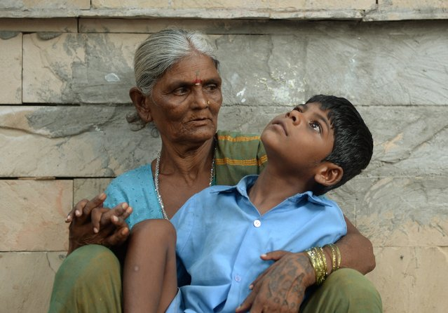 In this photograph taken on May 20, 2014 nine year old Indian boy Lakhan Kale sits with his grandmother on the pavement in Mumbai. (Photo by Punit Paranjpe/AFP Photo)